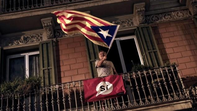 رجل يلوح بعلم 'إستيلادا' (العلم الكاتالوني الذي يستخدمه مؤيدو الاستقلال) من شرفة بعد إغلاق محطة الإقتراع 'مركز الشبيبة لا فونتانا'، 1 أكتوبر، 2017 في برشلونة. (AFP PHOTO / PAU BARRENA)