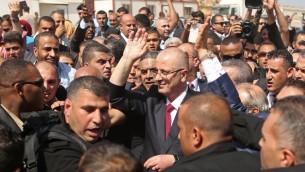رئيس الحكومة الفلسطيني رام الحمد الله (وسط الصورة) محاط برجال الأمن عند وصوله إلى معبر إيريز الحدودي في بيت حانون شمال قطاع غزة، 2 أكتوبر، 2017، في زيارة أولى إلى القطاع لإجراء محادثات تهدف إلى التوصل إلى اتفاق مصالحة بين حركتي فتح وحماس. (AFP PHOTO / MAHMUD HAMS)
