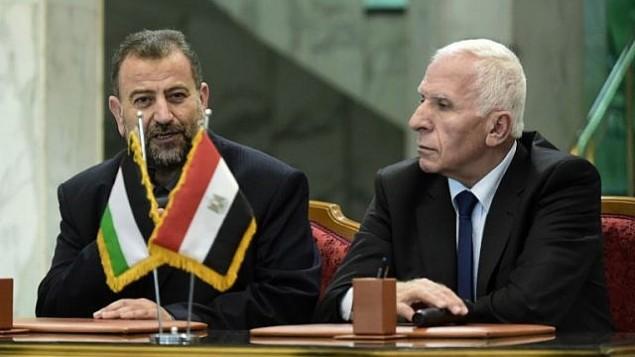 المسؤول في حركة 'فتح' عزام الأحمد، من اليمين، والمسؤول في 'حماس' صالح العاروري، من اليسار، يتحدثان للصحافيين بعد التوقيع على اتفاق مصالحة في القاهرة، 12 أكتوبر، 2017. (AFP/Khaled Desouki)