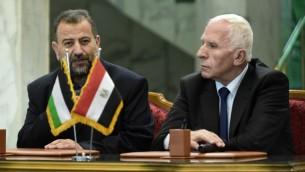 عزام الاحمد من حركة فتح (يمين) وصالح العاروري من حركة حماس، يتحدثان مع الصحافة بعد التوقيع على اتفاق المصالحة بين الفصيلين في القاهرة، 12 اكتوبر 2017 (AFP/Khaled Desouki)