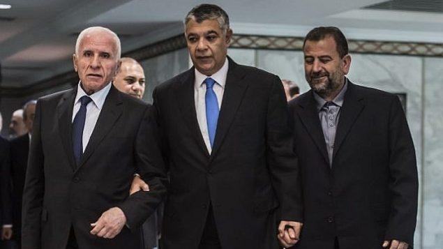 رئيس جهاز المخابرات المصرية خالد فوزي، وسط الصورة، يصل برفقة المسؤول في حركة 'فتح' عزام الأحمد، من اليسار، والمسؤول في 'حماس' صالح العاروري، من اليمين، قبل التوقيع  على اتفاق المصالحة في القاهرة في 12 أكتوبر، 2017. (AFP/ KHALED DESOUKI)