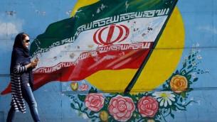 سيدة إيرانية تمر من أمام رسم للعلم الإيراني على جدار في العاصمة طهران، 14 أكتوبر، 2017. (AFP PHOTO / STR)