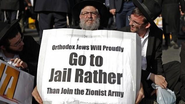 يهودي حريدي يحمل لافتة خلال تظاهرة في القدس ضد تجنيد اليهود الحريدم في الجيش الإسرائيلي، 19 أكتوبر، 2017. (AFP Photo/Thomas Coex)