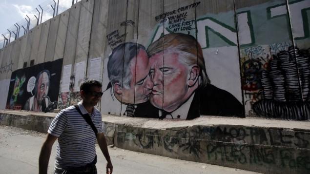 سائج يمشي امام جدارية للفنان لاشساكس تظهر اللرئيس الامريكي دونالد ترامب بتبادل القبل مع رئيس الوزراء الإسرائيلي بنيامين نتنياهو على الجدار الفاصل بين مدينة بيت لحم في الضفة الغربية ومدينة القدس، 29 اكتوبر 2017 (AFP PHOTO / Musa AL SHAER)