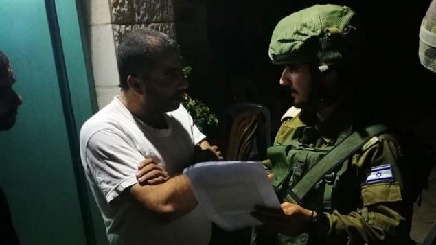 جنود يقدمون اوامر هدم منزل معتدي قتل ثلاثة حراس امنيين الى افراد عائلته في بلدة بيت سوريك في الضفة الغربية، 3 اكتوبر 2017 (Israel Defense Forces)