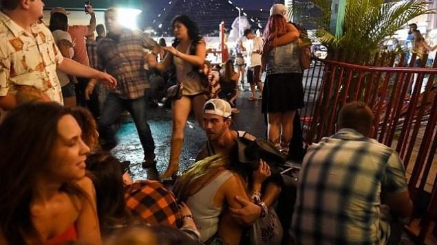 أشخاص يحاولون الإختباء خلال حفل  Route 91 Harvest الموسيقي بعد سماع دوي إطلاق نار في 1 أكتوبر، 2017، في لاس فيغاس، ولاية نيفادا.  (David Becker/Getty Images/AFP)