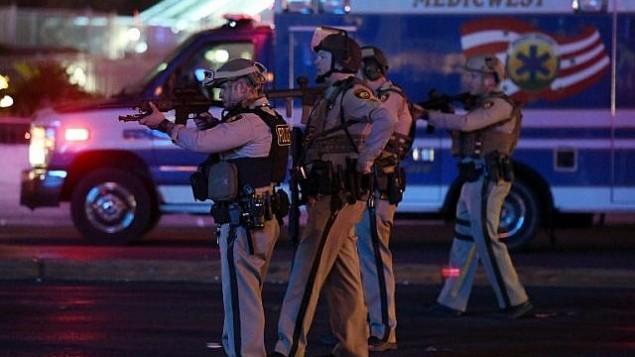 رجال شرطة يصوبون أسلحتهم باتجاه سيارة تسير بالقرب من التقاطع بين جادة 'تروبيكانا' وجادة 'لاس فيغاس' بعد هجوم إطلاق نار في حفل موسيقي في 2 أكتوبر، 2017، في مدينة لاس فيغاس بولاية نيفادا. (Ethan Miller/Getty Images/AFP)