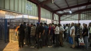 عمال فلسطينيون ينتظون عبر نقطة التفتيش من مدينة رام الله في الضفة الغربية للعمل في إسرائيل، 4 يونيو، 2013. (Yonatan Sindel/Flash90)