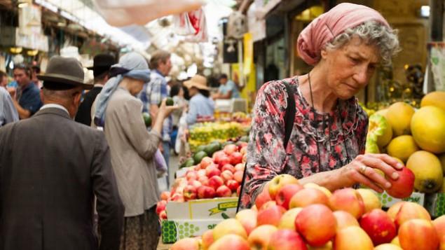 سيدة تختار التفاح في سوق محانيه يهودا في القدس، 16 يونيو، 2015. (Micah Bond/FLASH90)