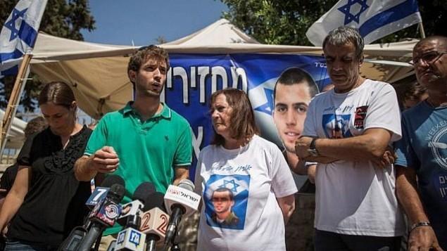 عائلتا الجنود الإسرائيليين الراحلين أورون شاول وهادار غولدين يتحدثان مع الصحافة في خيمة الاحتجاج خارج مقر إقامة رئيس الوزراء بنيامين نتنياهو في القدس في 29 يونيو / حزيران 2016. (Hadas Parush/Flash90)