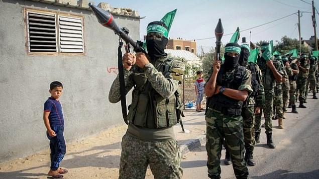 عناصر من 'كتائب عز الدين القسام'، الجناح العسكري لحركة 'حماس'، يشاركون في مسيرة لإحياء الذكرى الثالثة لعملية 'الجرف الصامد'، 20 يوليو، 2017، في خان يونس، جنوب قطاع غزة.(Abed Rahim Khatib/ Flash90)