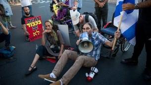 نشطاء معاقون يقومون بإلاق شارع 'أبن غافيرول' في تل أبيب في اطار احتجاجات تدعو إلى زيادة مخصصات المحكومة، 31 أغسطس، 2017. (Miriam Alster/Flash90)