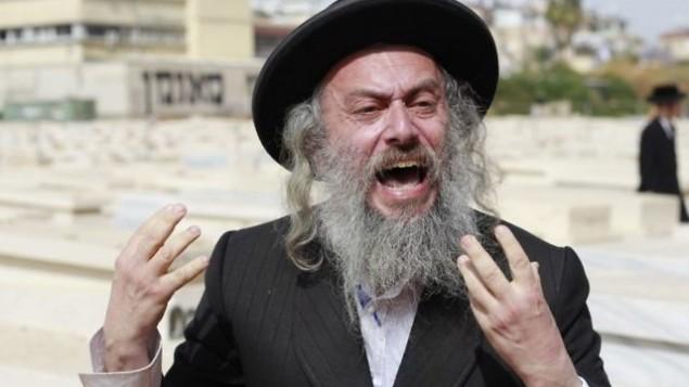 يصرخ متظاهر اورثوذكسي على الناس الذين يحضرون مراسم للجنود الأرثوذكس الذين سقطوا في مقبرة في مدينة بني براك في الأول من مايو عام 2017، يوم الذكرى الإسرائيلي. (Judah Ari Gross/Times of Israel)