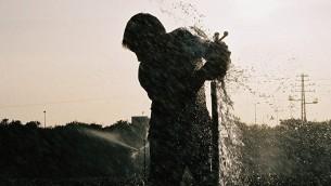 رجل يصلح رشاشة مياه في حقل في عيميك خيفر. (illustrative photo: Gili Yaari /Flash90)