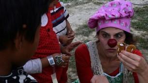 مهرجة طبية إسرائيلي تقوم بالترفية عن ضحايا الزلزال في نيبال خلال زيارة إلى معكسر مؤقت للحيش قس 6 مايو، 2015. (AFP/PRAKASH MATHEMA)