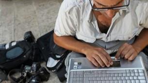 رجل يستخدم حاسوب نقال. (Nati Shohat/Flash90)