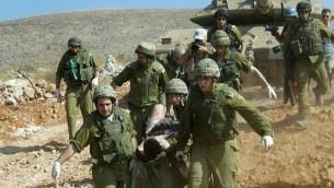 جنود يقومون بإخلاء رفيقهم المصاب خلال حرب لبنان الثانية، في 24 يوليو، 2006. (Haim Azoulay/ Flash 90/ File)