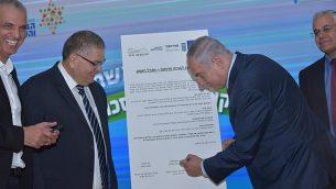 رئيس الوزراء بينيامين نتنياهو (من اليمين) يوقع على اتفاق لمشروع سكني جديد في مدينة مجدال هعيمق شمال البلاد، 6 نوفمبر، 2017. (Migdal Haemek)