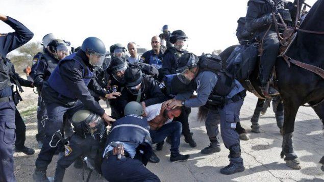 عناصر الشرطة الإسرائيلية تعتقل رجلا بدويا خلال مظاهرات ضد هدم منازل في قرية ام الحيران البدوية غير المعترف بها، 18 يناير 2017 (AFP/AHMAD GHARABLI)