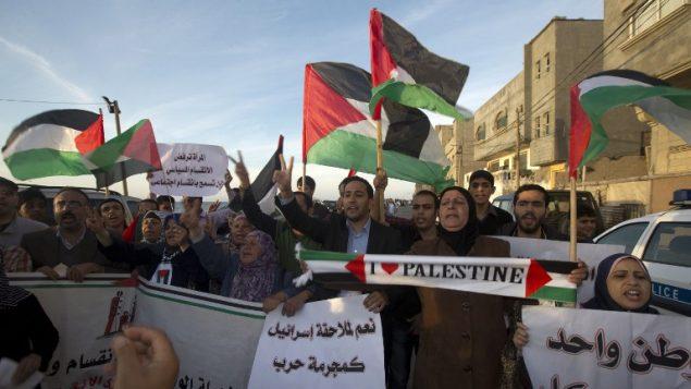 فلسطينيون يلوحون باعلام فلسطينية خلال مظاهرة في غزة، 22 ابريل 2014 (AFP/Mahmud Hams)