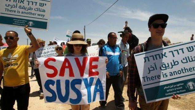 ناشطون فلسطينيون، اجانب واسرائيليون يتظاهرون في قرية سوسيا في الضفة الغربية ضد هدم القرية الفلسطينية الواقعة في تلال الخليل، 5 يونيو 2015 (AFP/Hazem Bader)