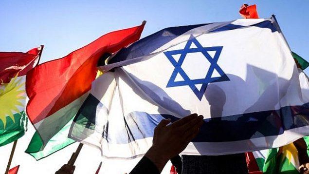 صورة تم التقاطها في 21 أكتوبر، 2017، تظهر رجلا يحمل العلم الإسرائيلي إلى جانب علام كردستان العراق خلال مظاهرة أمام مكتب الأمم المتحدة في إربيل، عاصمة الإقليم الذي يتمتع بالحكم الذاتي. (AFP Photo/Safin Hamed)