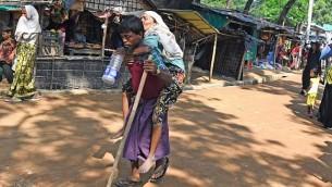 يحمل لاجئ من الروهينغا امرأة مسنة نحو مأوى مؤقت في مخيم كوتوبالونج للاجئين في منطقة أوخيا البنغلاديشية، 26 أكتوبر / تشرين الأول 2017. (AFP/Tauseef MUSTAFA)