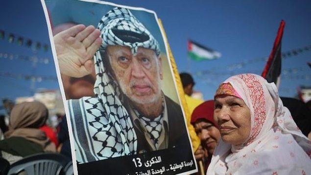 فلسطينيون يحملون صورا للزعيم الراحل ياسر عرفات في مدينة غزة في 9 نوفمبر، 2017، خلال مهرجات لإحياء الذكرى ال13 لوفاته. (AFP PHOTO / MOHAMMED ABED)