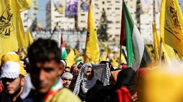 مناصرو حركة 'فتح' يلوحون بأعلام الحركة خلال مشاركتهم في مهرجان في مدينة غزة، 11 نوفمبر، 2017. (AFP/MAHMUD HAMS)