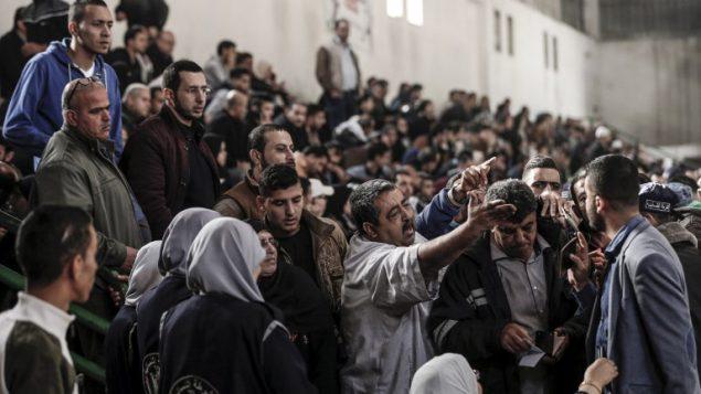 فلسطينيون يتشاجرون مع مسؤولين من حركة حماس في خان يونس اثناء الانتظار لركوب حافلات تنقلهم عبر معبر رفح الحدودي مع مصر، بعد افتتاحه لثلاث ايام لأول مرة بعد تحقيق اتفاق المصالحة الفلسطينية، 18 نوفمبر 2017 (AFP PHOTO / Mahmud Hams)