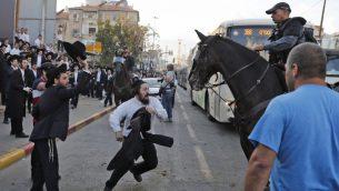 شرطي يفرق مظاهرة لليهود المتشددين ضد التجنيد العسكري في بني براك، 20 نوفبمر 2017 (AFP Photo/Ahmad Gharabli)
