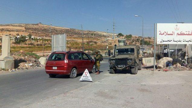 يقوم الجنود الإسرائيليون بتشغيل حاجز على مدخل قرية حلحول، مسقط رأس المهاجم الذي دهس إسرائيليين في وقت سابق من يوم 17 نوفمبر / تشرين الثاني 2017. (Israel Defense Forces)