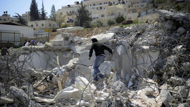 صورة توضيحية لرجل فلسطيني فوق حطام منزل تم هدمه في حي الطور في القدس الشرقية، 26 مارس 2014 (Sliman Khader/Flash90)