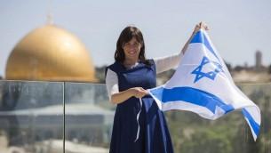 من نقطة بالقرب من الحرم القدسي، تسيبي حوتوفلي، الآن نائبة وزير الخارجية الإسرائيلي، ترفع العلم الإسرائيلي، مع قبة الصخرة في الخلفية، مايو 2014. (Yonatan Sindel/Flash90)