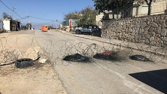 مستوطنون إسرائيليون يضعون حواجز مشتعله وأسلاك شائطة لمنع قوات الأمن من إخلائهم من  بؤرة نتيف هأفوت الاستيطانية غير القانونية في الضفة الغربية، 29 نوفمبر، 2017. (Times of Israel)
