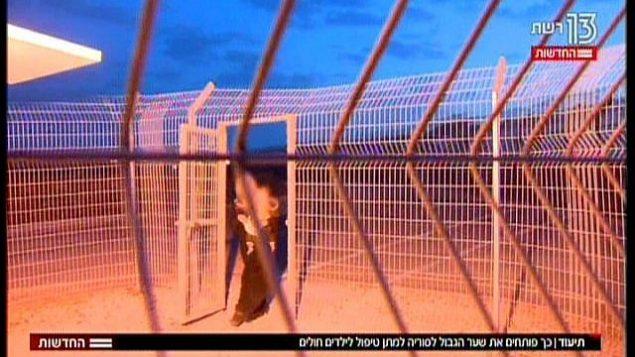 أم سورية، تحمل طفلها الصغير، تعبر الحدود إلى داخل إسرائيل،  في تقرير تلفزيوني تم بثه في 19 نوفمبر، 2017. (Hadashot News screenshot)