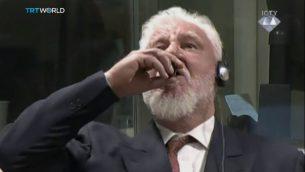 سولوبدان برالياك يتجرع ما يبدو كسم عند تلقيه حكم بالسجن 20 عاما في لاهاي، 29 نوفمبر 2017