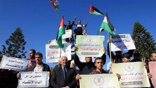 فلسطينيون يلوحون بالعلم الفلسطيني خلال مظاهرة في غزة دعما لمفاوضات المصالحة بين حماس وفتح، 3 ديسمبر 2017 (AFP/Mohammed Abed)