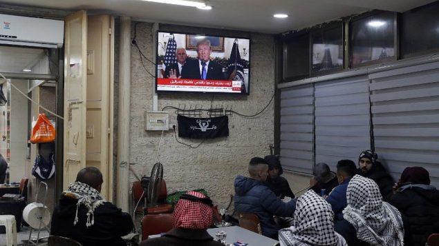 فلسطينيون يشاهدون خطاب الرئيس الامريكي دونالد ترامب بخصوص القدس داخل مقهى في المدينة، 6 ديسمبر 2017 (Ahmad GHARABLI/AFP)