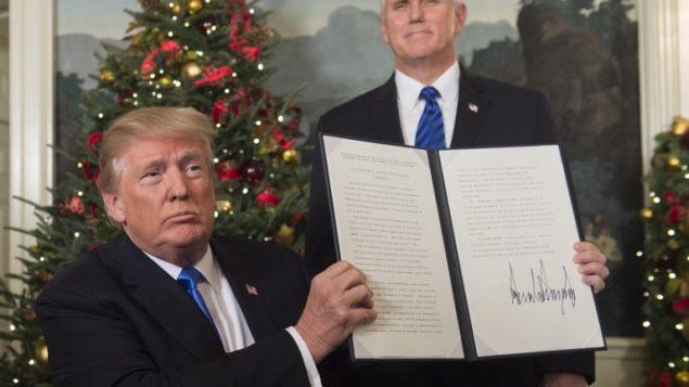 الرئيس الأمريكي دونالد ترامب يحمل مذكرة وقع عليها بعد أن أدلى ببيان حول القدس من غرفة الاستقبال الدبلوماسية في البيت الأبيض في العاصمة الأمريكية واشنطن، 6 ديسمبر، 2017، ونائب الرئيس مايك بنس يقف وراءه. (Saul Loeb/AFP)