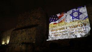 العلم الأميركي مع العلم الإسرائيلي على جدران المدينة القديمة في القدس، 6 ديسمبر 2017 (AFP/Ahmad GHARABLI)
