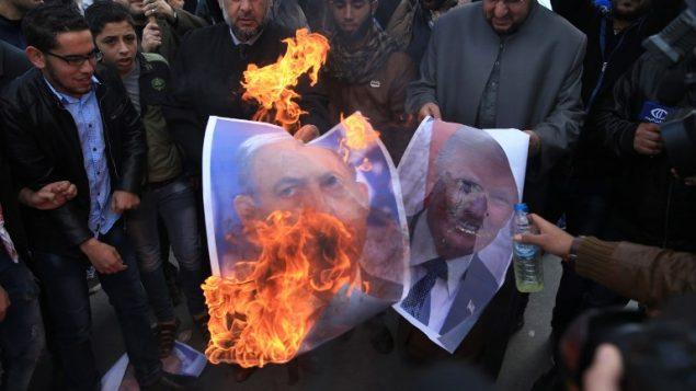 متظاهرون فلسطينيون في غزة يحرقون صور الرئيس الامريكي دونالد ترامب ورئيس الوزراء بنيامين نتنياهو في اعقاب قرار ترامب الاعتراف بالقدس كعاصمة اسرائيل، 7 ديسمبر 2017 (AFP PHOTO / MOHAMMED ABED)