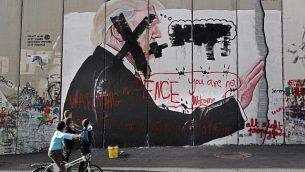 أطفال فلسطينيون ينظرون إلى رسم غرافيتي للرئيس الأمريكي دونالد ترامب وشعارات ضد نائب الرئيس مايك بنس على الجدار الفاصل الإسرائيلي في مدينة بيت لحم في الضفة الغربية خلال مواجهات بين محتجين فلسطينيين والقوات الإسرائيلية عند حاجز إسرائيلي، 7 ديسمبر، 2017. (AFP/Thomas Coex)