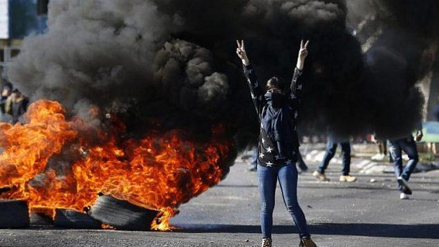 متظاهرة فلسطينية ملثمة خلال اشتباكات مع جنود اسرائيليين امام حاجز بالقرب من رام الله في الضفة الغربية، 8 ديسمبر 2017 (AFP PHOTO / ABBAS MOMANI)