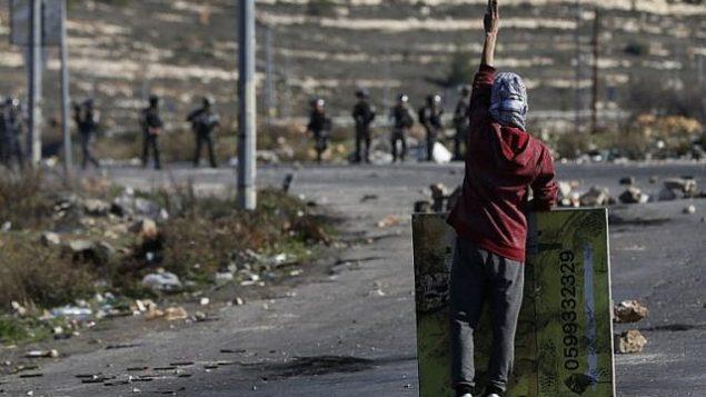 متظاهر فلسطيني ملثم خلال اشتباكات مع جنود اسرائيليين امام حاجز بالقرب من رام الله في الضفة الغربية، 8 ديسمبر 2017 (AFP PHOTO / ABBAS MOMANI)