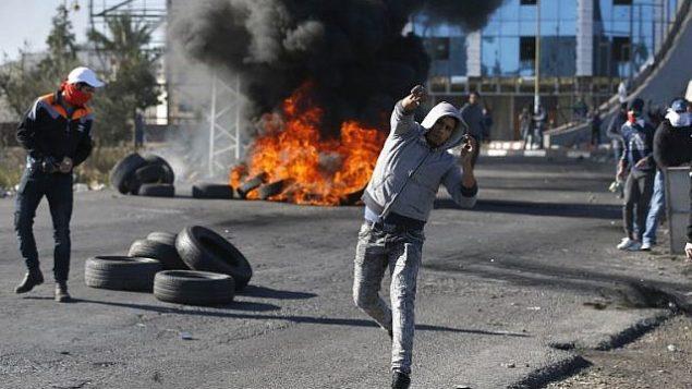 متظاهرون فلسطينيون يرشقون الحجارة باتجاه جنود اسرائيليين امام حاجز بالقرب من رام الله في الضفة الغربية، 8 ديسمبر 2017 (AFP PHOTO / ABBAS MOMANI)