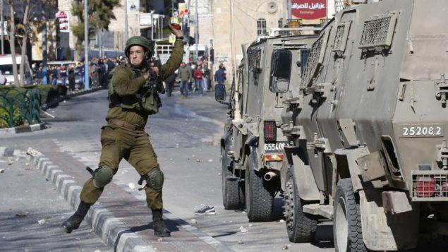 جندي اسرائيلي يلقي قنبلة صوت باتجاه متظاهرين فلسطينيين خلال مواجهات في الخليل، 8 ديسمبر 2017 (Hazem Bader/AFP)