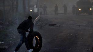 متظاهر فلسطيني يدفع بإطار مشتعل باتجاه القوات الإسرائيلية خلال مواجهات في مدينة نابلس في الضفة الغربية، في 9 ديسمبر، 2017، في أعقاب تظاهرات ضد قرار الرئيس الأمريكي دونالد ترامب الإعتراف بالقدس عاصمة لإسرائيل. (AFP PHOTO/ AAFAR ASHTIYEH)