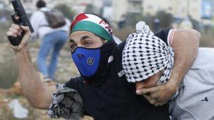 شرطي اسرائيلي مستعرب يعتقل متظاهرا فلسطينيا خلال مواجهات في مدينة رام الله في الضفة الغربية، 13 ديسمبر 2017 (Abbas Momani/AFP)