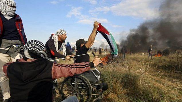 المتظاهر الفلسطيني المقعد ابراهيم ابو ثريا يلوح بالعلم الفلسطيني خلال مظاهرة امام السياج الحدودي مع اسرائيل، 15 ديسمبر 2017 (MOHAMMED ABED / AFP)